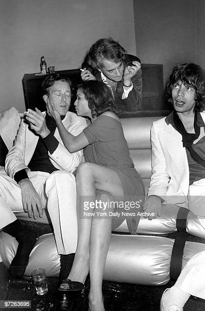 Fashion designer Halston is comforted by Bianca Jagger as husband Mick looks on at birthday bash for Bianca at Studio 54.