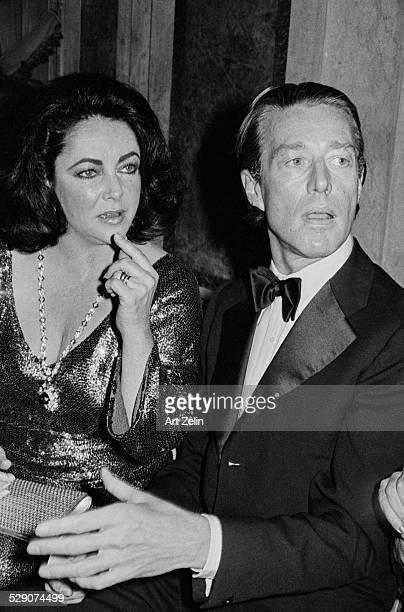 Fashion designer, Halston, with Elizabeth Taylor at a formal event, New York, circa 1975.