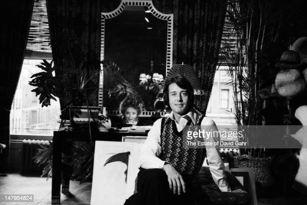Fashion designer Halston , with fashion model Heidi Goldman in the background, poses for a photograph at home on September 9, 1969 in New York City.