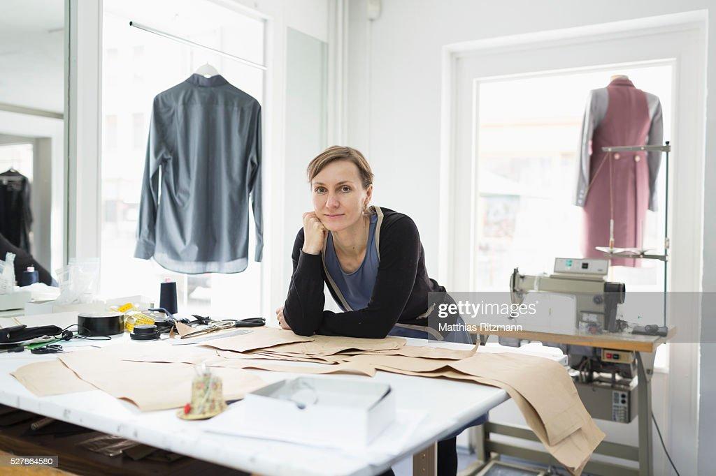 Fashion designer in her atelier at desktop : Stock Photo