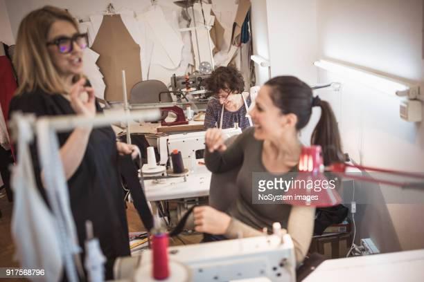 Mode-Designer in ihrem Atelier kontrollieren Mitarbeiter