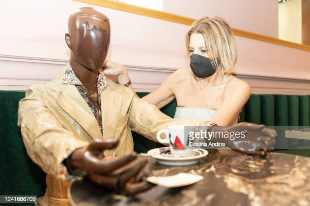 Fashion designer Inés Penelas poses next to a dressed mannequin to show the latest fashion trends while ensuring social distancing in the cafeteria...