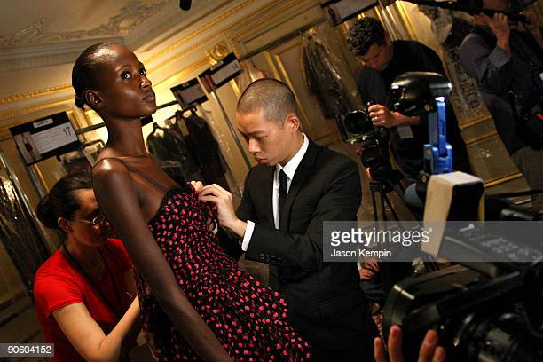 Fashion designer Jason Wu makes adjustments to a model's gown backstage before the Jason Wu Spring 2010 Fashion Show at the St. Regis Hotel on...