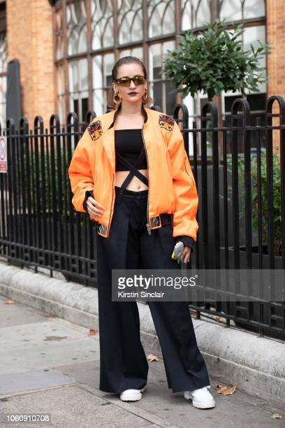 Fashion Designer Jeanne Touzet wears an Asger Juel Larsen jacket Max Mara trousers Dr Martens shoes and Chanel earrings during London Fashion Week...