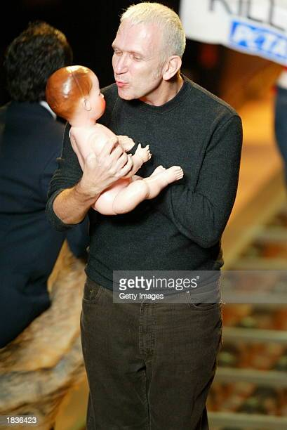 Fashion designer Jean-Paul Gaultier holds a baby doll during their Fall/Winter 2004 ready-to-wear collection March 8, 2003 in Paris.