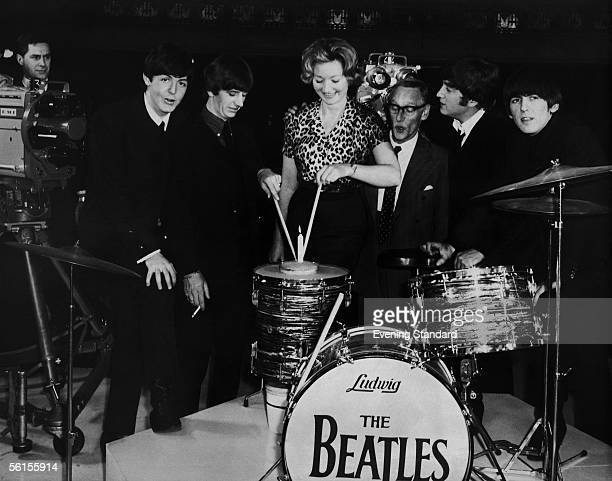 Fashion designer Julie Harris is presented with a birthday cake by The Beatles and Wilfred Brambell at the Scala Theatre where they are all working...