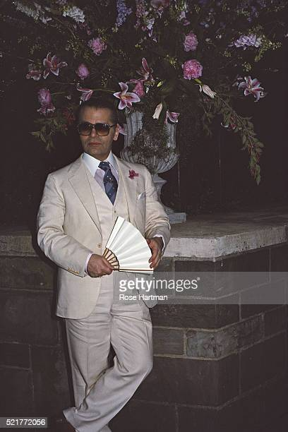 Fashion designer Karl Lagerfeld leans against a low wall New York New York 1988