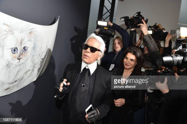 Fashion designer Karl Lagerfeld stands next to a drawinf of his Birman cat at the vernissage for his photo calender 'Corsa Karl and Choupette' at the...