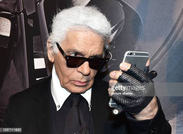 Fashion designer Karl Lagerfeld stands watching his smartphone at the vernissage for his photo calender 'Corsa Karl and Choupette' at the Palazzo...