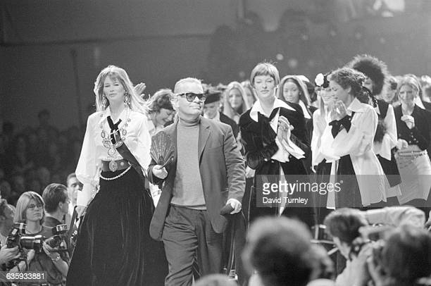 Fashion designer Karl Lagerfeld surrounded by super models struts down the cat walk for his curtain call