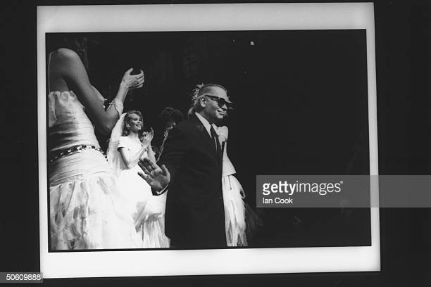 Fashion designer Karl Lagerfeld w model Claudia Schiffer wearing one of his creations clapping behind him at Chanel spring show