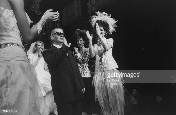 Fashion designer Karl Lagerfeld w supermodels Linda Evangelista Claudia Schiffer wearing his creations clapping behind him at Chanel spring show