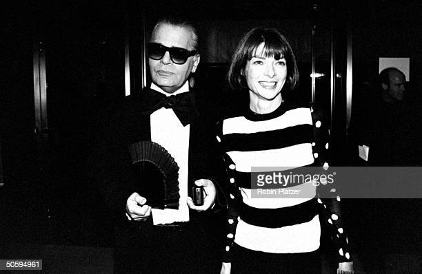 Fashion designer Karl Lagerfeld wearing tuxedo w large bow tie holding hand fan posing w VOGUE publisher Anna Wintour at the 12th annual Council of...