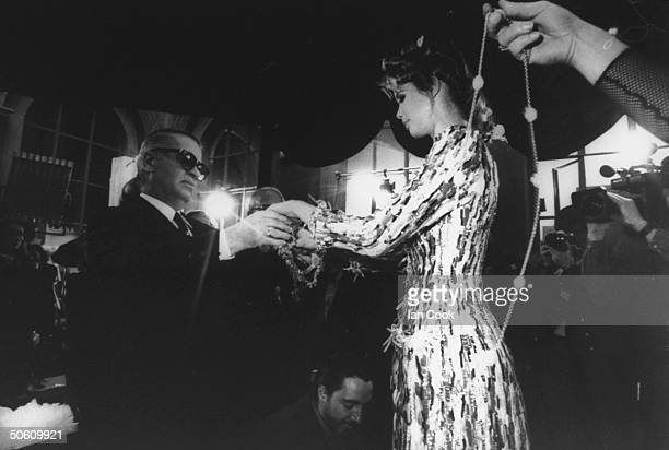 Fashion designer Karl Lagerfeld wrapping his model Claudia Schiffer w his trademark chains before she enters runway at Chanel Spring show