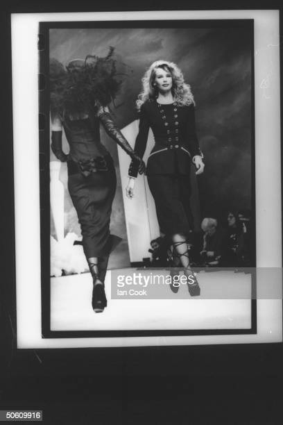 Fashion designer Karl Lagerfeld's model Claudia Schiffer wearing snugfitting long jacket w long skirt highroped shoes on runway at Chanel Spring show