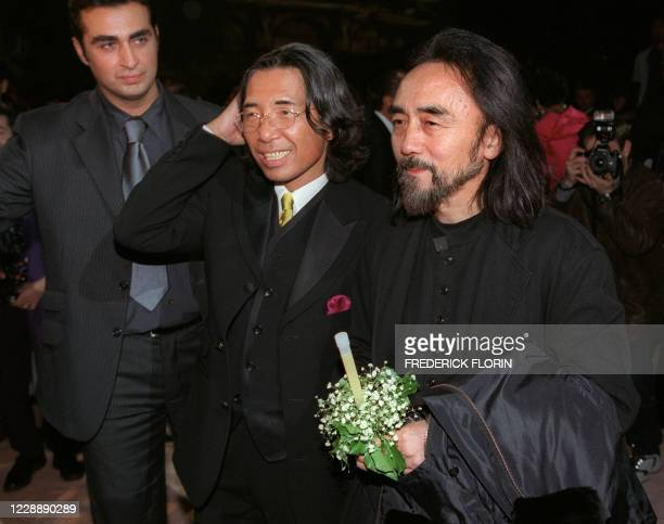 Fashion designer Kenzo smiles next to Yohji Yamamoto , late 07 October 1999 at the Zenith, one of Paris premier rock venues, following his final...