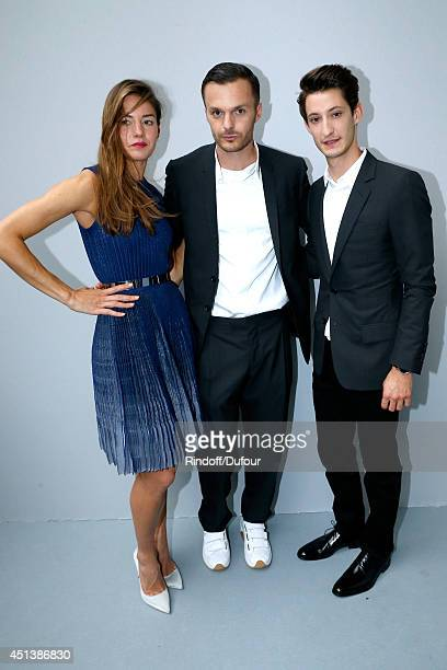 Fashion designer Kris Van Assche poses backstage with Pierre Niney and his companion Natasha Andrews after the Dior Homme show as part of the Paris...
