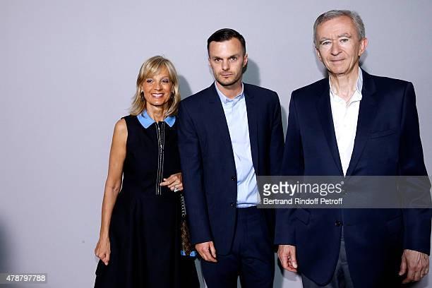 Fashion designer Kris Van Assche standing between Owner of LVMH Luxury Group Bernard Arnault and his wife Helene Arnault pose Backstage after the...