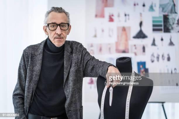mode-designer leht locker an einer ankleidepuppe - designer einrichtung stock-fotos und bilder