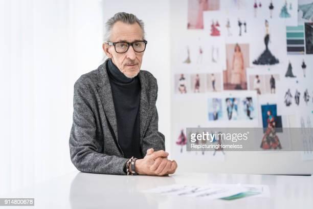 Mode-Designer lehnt sich auf einem Tisch ab