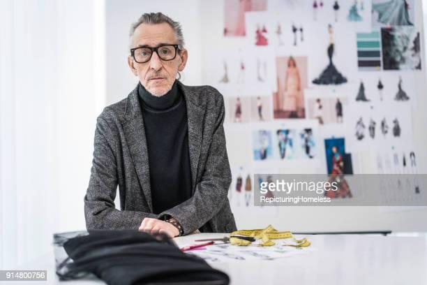 Mode-Designer lehnt sich auf einem Tisch ab und fokussiert sich auf die Kamera