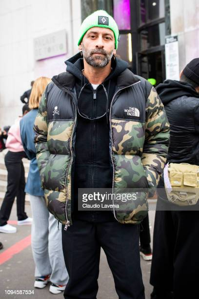 Fashion designer Marcelo Burlon wearing The North Face camouflage bomber and a green knit cap is seen in the streets of Paris before the Heron...