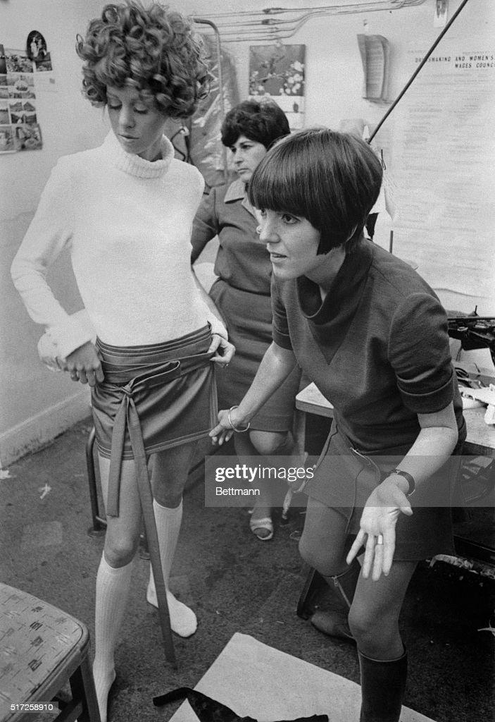 Fashion designer Mary Quant adjusts a miniskirt on a fashion model.