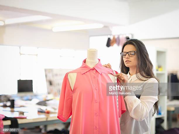 Fashion designer measuring garment in fashion design studio