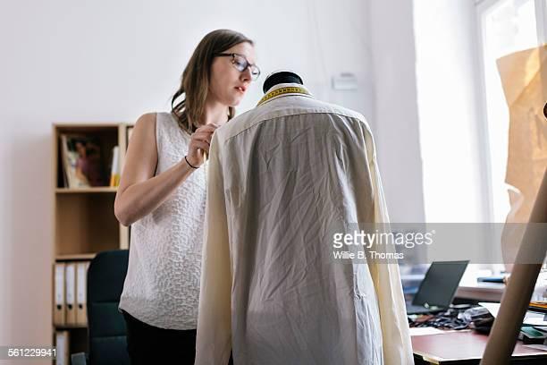 Fashion designer measuring garment