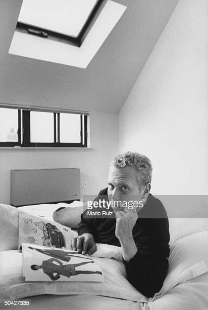 Fashion designer Michael Kors lying on bed w a fashion magazine in bedroom of his penthouse