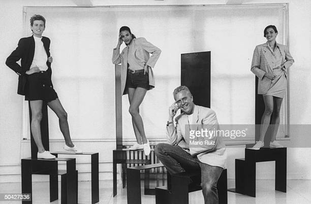 Fashion designer Michael Kors posing in front of three female models on pedestals showing off his sports fashions incl short skirts jacket ensembles...