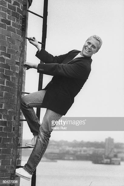 Fashion designer Michael Kors standing on ladder on the terrace of his penthouse