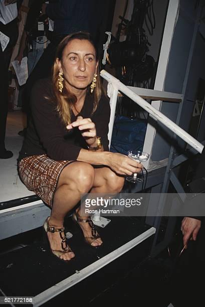 Fashion designer Miuccia Prada sits on a step with a glass as she attends a Miu Miu show, New York, New York, 1996.