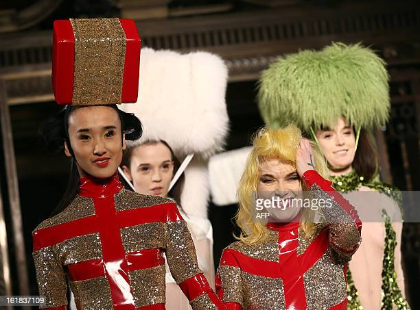 Fashion designer Pam Hogg walks down the catwalk with a model to greet the audience after her show at the 2013 Autumn/Winter London Fashion Week in...