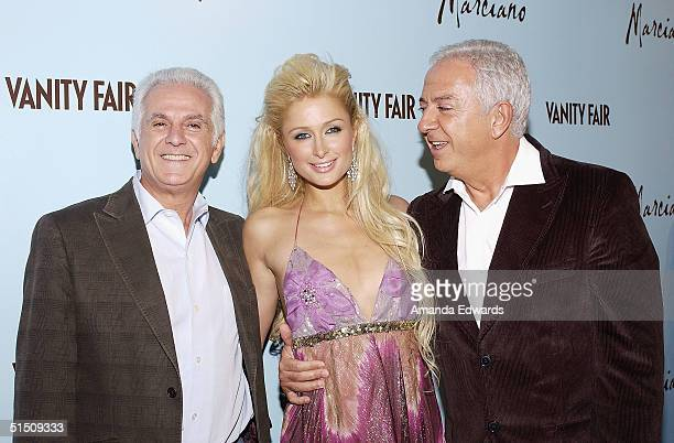 Fashion Designer Paul Marciano model Paris Hilton and Maurice Marciano arrive at the launch of Marciano hosted by Vanity Fair on October 19 2004 at...