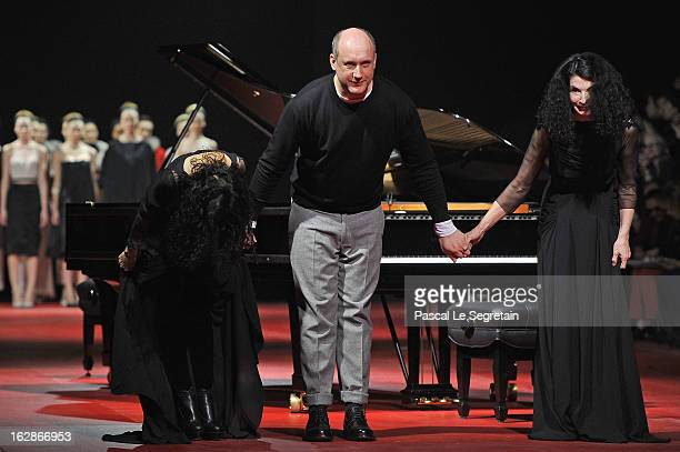 Fashion designer Peter Copping center escorted by pianists sisters Katia and Marielle Labeque acknowledge applause following the Nina Ricci...