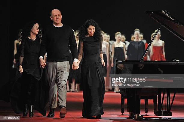 Fashion designer Peter Copping escorted by pianists sisters Katia and Marielle Labeque acknowledge applause following the Nina Ricci Fall/Winter 2013...