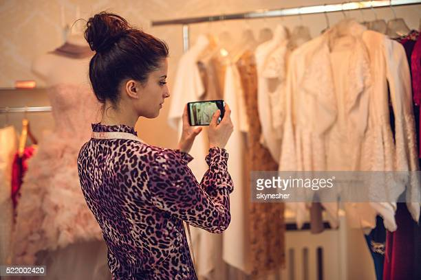 Fashion designer photographing clothes in her clothing store.