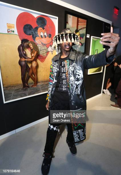 Fashion designer Phree Hester of Los Angeles makes a selfie with artwork by Deana Lawson titled 'Mickey Friends' at the Bacardi No Commission Marquee...