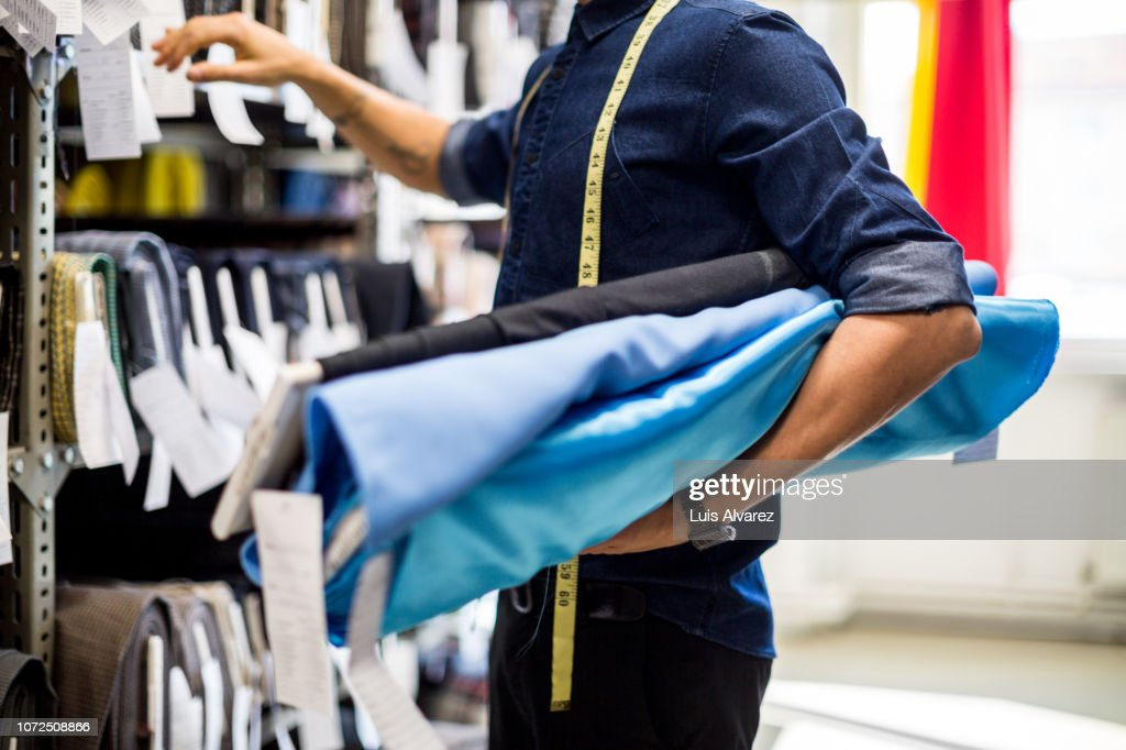 Fashion designer picking the fabric rolls from the rack : Stock Photo