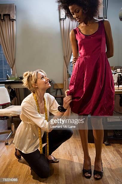 Fashion designer pinning female model's dress, smiling