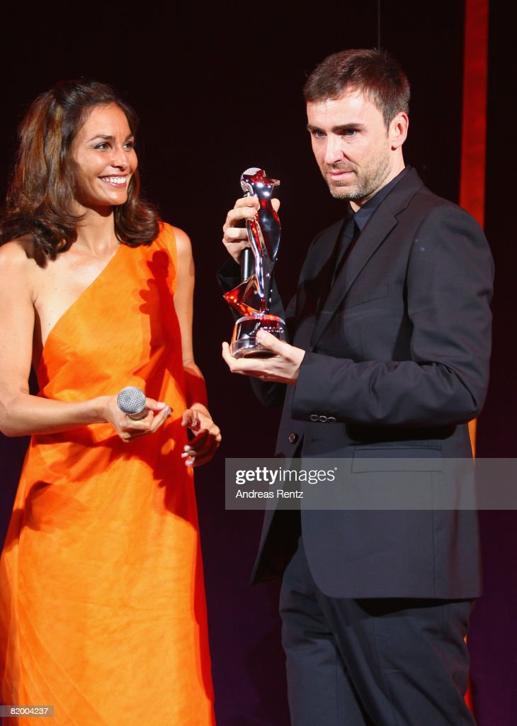 Fashion designer Raf Simons (R) receives the ELLE Fashion Star newcomer award from Ines Sastre (L) at the ELLE Fashion Star award ceremony during Mercedes Benz Fashion Week Spring/Summer 2009 at the Tempodrom on July 19, 2008 in Berlin, Germany.