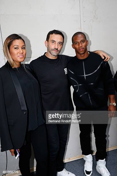 Fashion designer Riccardo Tisci poses backstage with American Football player Victor Cruz and his companion Elaina Watley after the Givenchy show as...