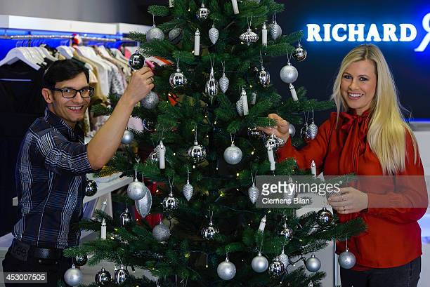 Fashion designer Richard Kravetz and TV host Nadine Krueger pose during a photo session in front of a christmas tree on December 01, 2013 in Berlin,...