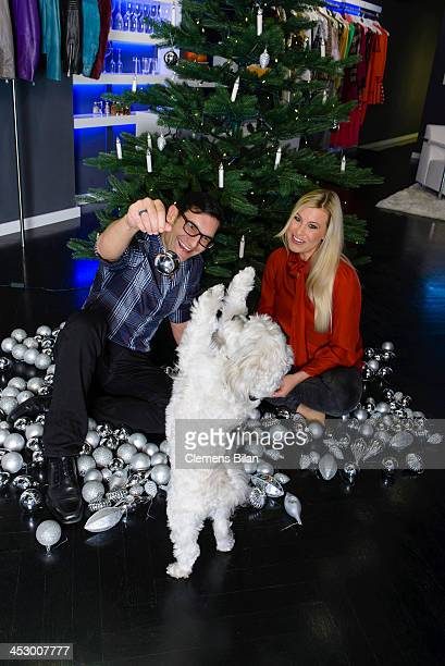 Fashion designer Richard Kravetz, his dog Coco and TV host Nadine Krueger pose during a photo session in front of a christmas tree on December 01,...