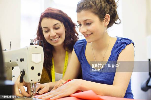Fashion designer sewing fabrics with assistant