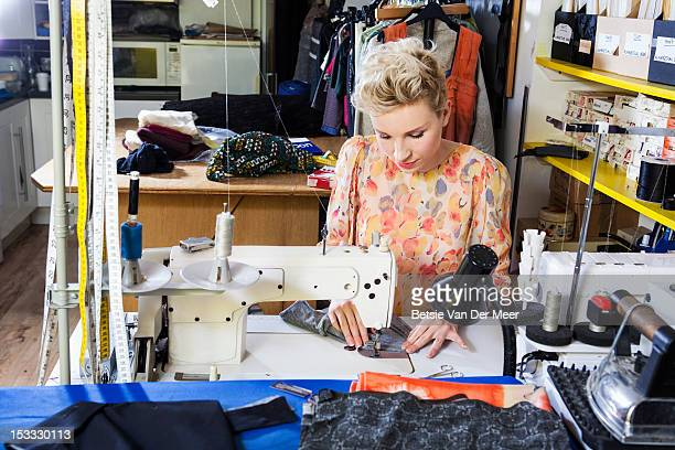 Fashion designer sewing on sewing machine.