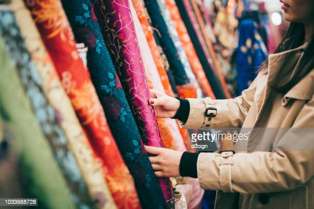 fashion designer shopping for colourful fabrics in fabric store - fashion hong kong stock photos and pictures
