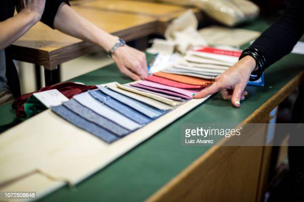 fashion designer showing the fabric swatch to the customer - fashion industry stock pictures, royalty-free photos & images