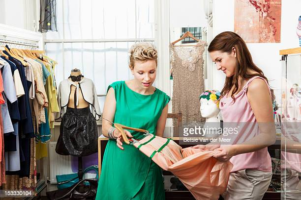 Fashion designer shows client skirt.